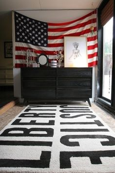 Americana - american flag hung on wall on top of black painted dresser and typographical black and white rug
