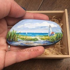 Lighthouse beach scene painted rock.
