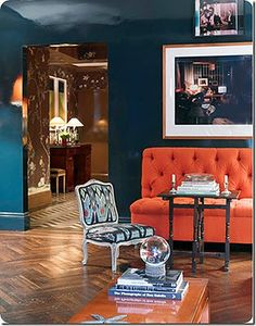 Teal walls accented with an orange couch