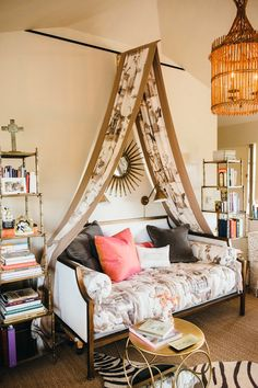 Frances' office, which can serve as a spare guest room in a pinch (daybed and etageres from Ballard Designs; bed cover and curtain, from Nina Campbell; birdcage chandelier from Visual Comfort). Her latest book (on table), The Bee Cottage Story, is now in its 6th printing. Photo by Cara Robbins.