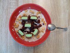 Ovesná kaše (ovesné vločky s mlékem) - posypaná oříšky, brusinkami, rozkrájená Deli tyčinka. Ideální snídaně.