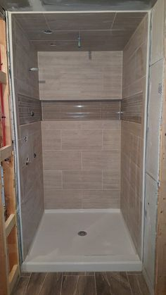 """Nice size shower with 12""""x24"""" tiles on walls and ceilings. Large built in Niche with mosaic accent strip."""