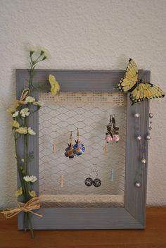 """Voici un autre cadre porte bijoux que j'ai appelé """"Fleur bleue"""". oui, je sais, les fleurs sont jaunes, mais le cadre bleuté et la mélancolie du jaune m'ont inspiré ce titre. La fonction est la même que le précédent : ranger vos bijoux en beauté. Vous pouvez en plus accrocher vos barrettes et petites pinces à cheveux sur la dentelle en bas. Vous pouvez aussi choisir d'en faire un porte photo. A poser ou à suspendre. Dimensions : 26 cm sur 31 cm. Prix : 15 euros"""