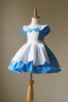 The Alice in Wonderland Costume is constructed of cotton fabric with a faux apron appliqued to the bodice. The Alice Dress also features a peter pan collar and flutter apron sleeves with a full attached apron that ties in the back in a full bow. It has a unique elasticized back,