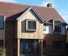 Clad parts with brick, grey aluminium windows and red tile roof.