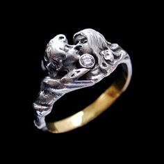 ART NOUVEAU BETROTHAL RING. A silver and 18 carat gold betrothal ring cast as lovers entwined in an embrace  cent red with a diamond. To one side the male is encircled by a serpent, a sign of eternity .    French. Circa 1910. Eagles head gold mark.