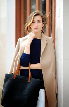Navy sweater, camel coat.