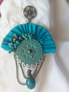 Cod-346 Turquoise shibori silk frame adorned with orichalcum ornaments and natural turquiose and sapphire stones.  https://www.facebook.com/Crown-Art-Jewelry-685629774912291