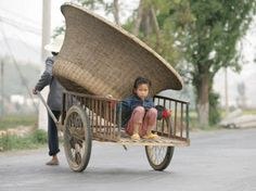 A woman farmer pulls her farm cart with basket  daughter on the road from Kunming to Da Li, Yunnan Province, China