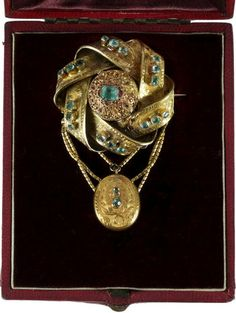 A Victorian gold and emerald brooch and a pendant and earrings ensuite The emerald set brooch of entwined knot design, with glazed locket compartment verso, suspending an oval pendant below, with chain festoons, cased, together with an onyx and seed pearl inset pendant with matching ear pendants (one a/f), first pendant length 6cm.