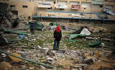 Garota palestina caminha por estádio de futebol que ficou destruído após ataque aéreo israelense, em Gaza.