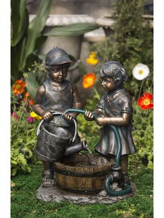 The Garden Hose and Kids Water Fountain features and adorable little bowl with baseball cap holding a watering can. The little girl stands beside him holding a garden hose, filling the watering can as