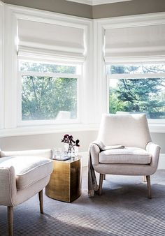 A living space with a gold coffee table, and midcentury modern creme armchairs