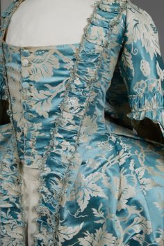 Open gown of Chinese cerulean blue silk woven with a large-scale white and platinum floral, having elbow length sleeve with lobed triple cuff gathered into a ruched band, square neckline, bodice front panel with self buttons, trimmed with furbelows edged in silk fly braid, sacque back, pleated skirt side panels with pocket slits, back lacing bodice lining in various cottons, the front printed in a red windowpane. B-32, W-24, L 52-64. (Lacking petticoat, minor losses to fly braid, slight wear…