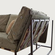 Military-esque couch with metal frames, a khaki covering and brown accents.