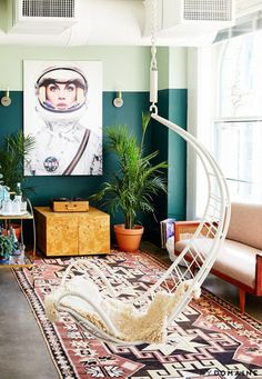 Loft living space with two-tone green painted walls, eclectic astronaut art, and a hanging rattan chair