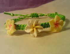 This handmade bracelet is made from bright green bamboo cording, with two small yellow and one small white polymer plumeria beads. Each