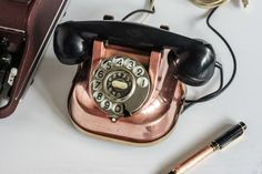 Beautiful Copper Bell telephone next to an Orbis-Olympia typewriter.