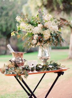 Pairing elegant silver vases with rustic, natural flower arrangements makes for a nice wedding reception decor combination.