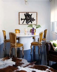 Love this, traditional chairs with modern table, cow hide rug, bold art...Nuevo Estilo revista de decoración