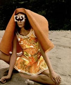 Pierre Cardin, 1971.  Either she's come up with an easy way to carry a tablecloth, or that outfit is going to leave some strange tan lines