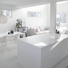 Suuri valkoinen keittiösaareke tarjoaa runsaasti työskentely- ja kokkaustilaa. Se korostaa myös upeasti tilan minimalistista valkoista värimaailmaa, josta löytyy myös Eames DSR tuolit ja Secto Design valaisin.