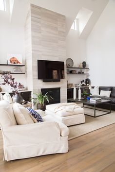 Living room remodel; seagrass rug, ottoman; floating shelves; fireplace; vein cut travertine | Interior Designer: Carla Aston / Photographer: Tori Aston