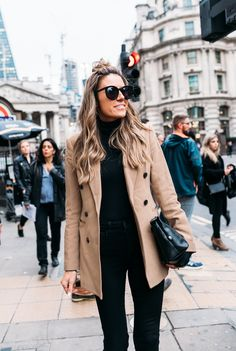 Black on black outfit with a classic camel coat