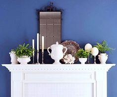 Nice arrangement for mantle or shelves, rhythm of white objects, silver, greenery.