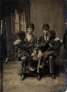 Tintype portrait of two white men, sitting, with two black boys, playing, ca. 1880,via the International Center of Photography