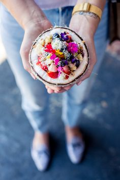 A beautiful and healthy Acai bowl served in a coconut and topped with edible flowers.