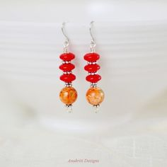 These boho style beaded dangle earrings are made with beautiful ceramic beads and Czech glass beads. The ceramic beads are a gorgeous shade of orange and have an abstract pattern of red and gold . The beads are accented with silver Tibetan spacers and hung on hypoallergenic nickel free ear wires. The abstract pattern on each bead is not identical but similar. These lightweight and comfortable earrings work with a variety of outfits and are great for casual and everyday wear. They would be…