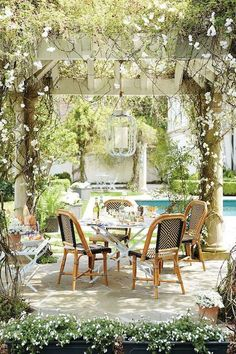 Amazing garden with pergola accented with a white lantern illuminating a round bistro table lined with French bistro chairs