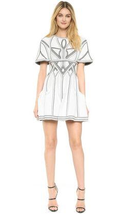 Thin panels with dot detailing crisscross this structured Herve Leger mini dress. The flounced skirt keeps the look feminine. Sleeveless. Hidden back zip. Unlined.