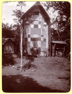 Photograph (black and white) from an album; Building with decorated front-wall. Ikot Udo Nto Ide, Nigeria, 6 November 1905. Gelatin silver print