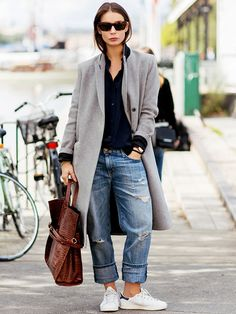 A perfectly undone look achieved by pairing boyfriend jeans with a loosely unbuttoned silk oxford and structured coat.