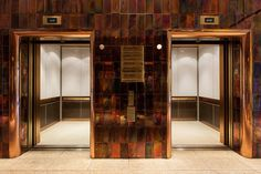 LEVELe-105 Elevator Interior with custom upper panel insets; lower panels in Bonded Bronze with Dark Patina and Modena pattern; handrail panels in Fused Bronze with Seastone finish; Rectangular handrail in Satin Bronze at Hilton Miami Airport Hotel, Miami, Florida