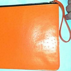 "Orange Tablet Clutch Made of faux ostrich skin, this clutch can fit a lot. There are no pockets or compartments allowing plenty of room for your wallet, small tablet, makeup etc. It measures 11.5"" across & 8.5""from top to bottom & has a zippered closure. It's bright orange color makes it the perfect accessory for spring & summer!  3/13 Alpha3 Bags Clutches & Wristlets"