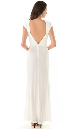 ISSA Cap Sleeve Open Back Gown - A minimalist gown in sweeping silk jersey. The bodice gathers at the waist, draping down the front of the skirt, and a deep V plunges to a hidden zip at the small of the back. Cap sleeves. Lined bodice. (Back view).