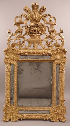 Very fine, French, Regence period mirror a parcloses: In solid, carved giltwood having original mercury glass and original gilding; the pediment ajouré (pierced). Circa 1720.