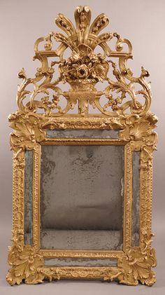 Espejo Muy fino, francés, Regence  En madera maciza, tallada dorada con vidrio de mercurio original y dorado original; El frontón ajouré (perforado). Hacia 1720.