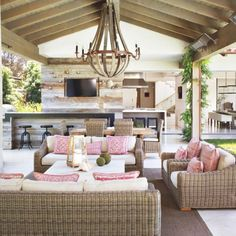 Designer Casey Browar created an open-air room to mimic a courtyard lifestyle. Touches of pink and a famhouse-glam vibe make this patio one of our favorites.