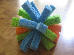 Splash Bomb  What you need:  3 plain kitchen sponges  Scissors  Strong string  Bucket and water  Take three slightly dampened sponges. Most come damp but if they're too dry, lightly dampen them.     Using your scissors, cut the sponges lengthwise into five individual strips.    Stack them up!  Then, simply tie a piece of the string around the center ... and pull tightly!     Finished product! Trim off the ends after you double knot it! Then let the games begin!