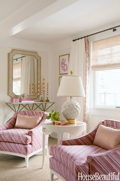 """The living room palette is drawn from vintage armchairs covered in Tulu's Lola stripe. """"It's the juiciest color combination — like cantaloupe, strawberry, and coconut jelly beans,"""" says designer Julie Kleiner. Made Goods' James mirror reflects the view. The table lamp is by Kristen Buckingham.      - HouseBeautiful.com"""