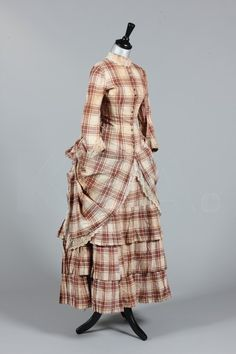 Item Description: A tartan cotton summer gown, circa 1875, princess-line with mother of pearl buttons, integral pleated skirt, the over skirt caught in a polonaised bustle, watch pocket to one hip, bust 76cm, 30in