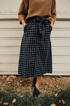 "Navy + Cream Grid Striped Midi Skirt Straight Cut + Faux Button Up Front Ribbon Waist Tie Hip Pockets Zippered Back High Waist Fit Runs Small If Between Sizes, Size Up View Size Chart Model is 5'9"" + Wearing a Medium"