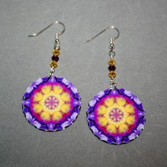 Dangle earrings adorned with my purple pansy boho chic mandala new age sacred geometry hippie kaleidoscope design titled Endearing Memories <br /> <br />These lightweight, dainty silver earrings begin with a dangle of two light topaz biscone Swarovski crystal beads and an amethyst biscone Swarovski crystal bead that accentuates the colors in the mandala charm that has%...