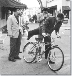 Hal Wallis and Hal Kanter present Elvis with his new 'Hound Dog' bike for use around the Paramount Studio complex.
