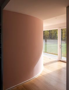 Also on the ground floor, the studio created a curved wall to enclose a new powder room while working around the windows. It is painted a pale pink. Pink Walls, White Walls, Black Window Frames, 1960s House, Wood Cladding, New York Studio, Outdoor Swimming Pool, Mid Century House, Large Windows