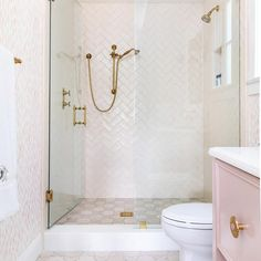This beautifully feminine bathroom features a seamless glass shower fitted with an antique brass shower kit mounted to pink herringbone surround tiels over white and pink floor tiles. Subway Tile Showers, Marble Showers, Subway Tiles, Shower Tiles, Bath Shower, Bathroom Wall, Bathroom Interior, Bathroom Ideas, Concrete Bathroom